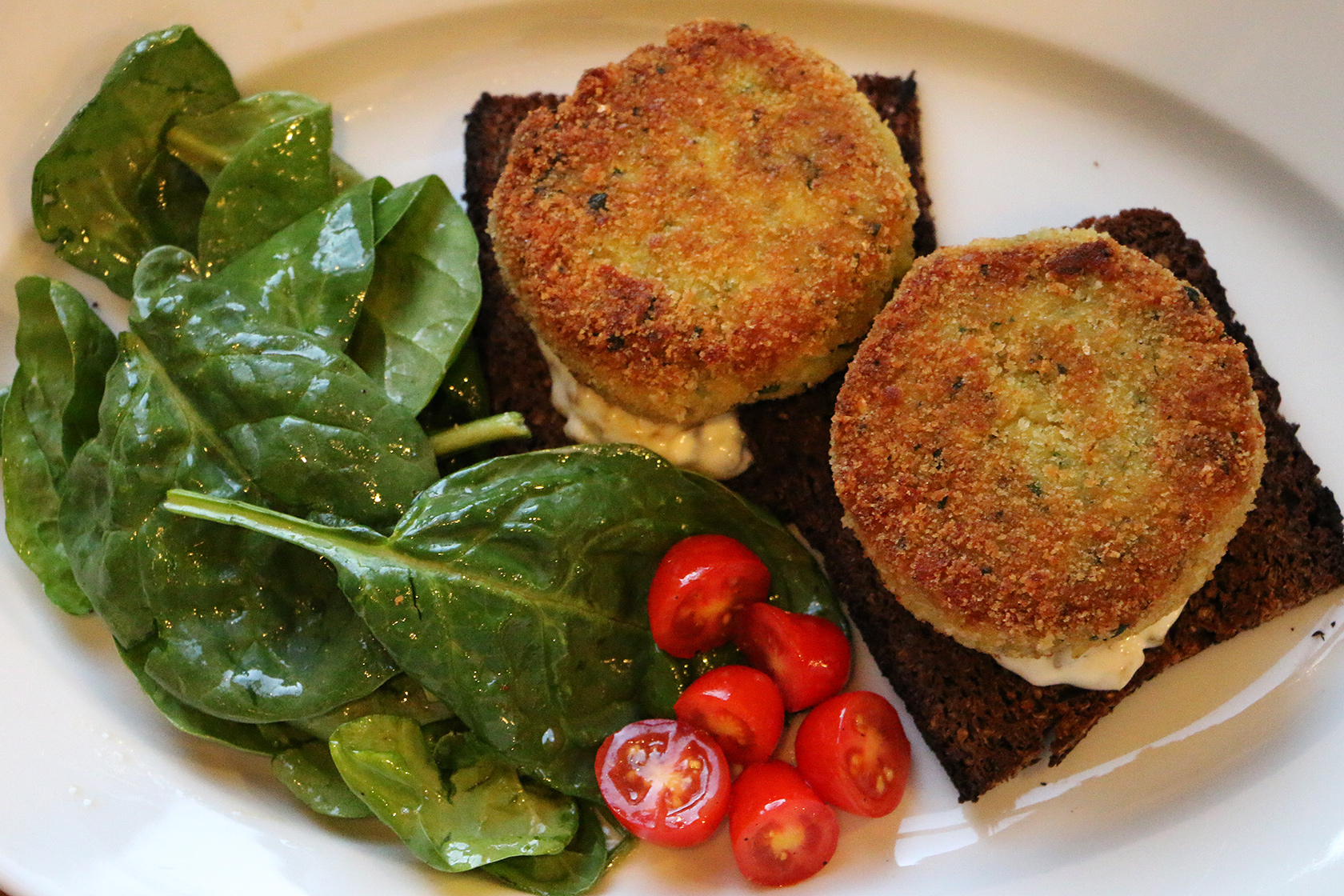 Salt Cod Fishcakes with tartar sauce, pumpernickel toast, and simple spinach salad